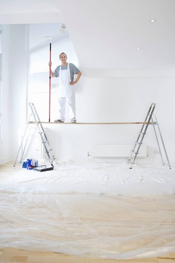 Stock Photo: 4208R-19915 Man standing on wood plank between ladders and holding paint roller in living room