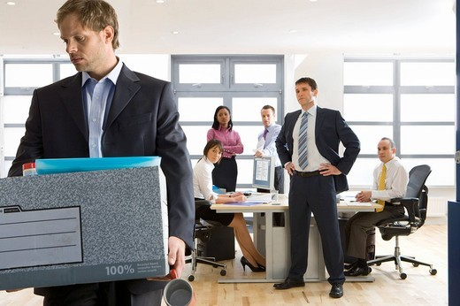 Business people watching businessman leave office with box of belongings : Stock Photo
