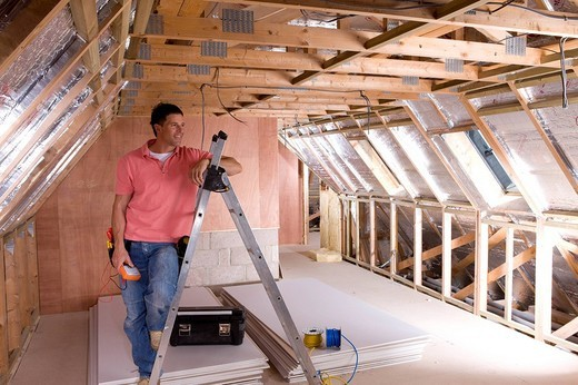 Stock Photo: 4208R-20107 Electrician leaning against ladder in attic under construction