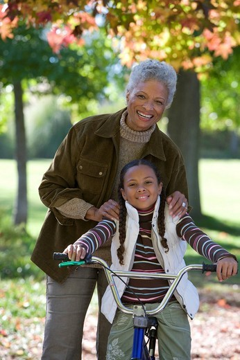 Stock Photo: 4208R-2015 Grandmother helping granddaughter learn to ride a bicycle