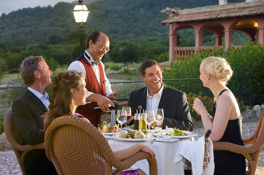 Waiter pouring wine for well_dressed couples at table on restaurant balcony : Stock Photo