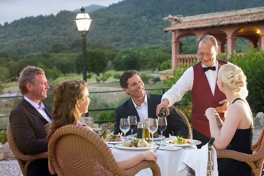 Stock Photo: 4208R-20238 Waiter pouring wine for well_dressed couples at table on restaurant balcony