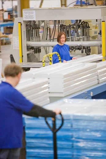 Workers processing and inspecting aluminium light fittings on production line in factory : Stock Photo