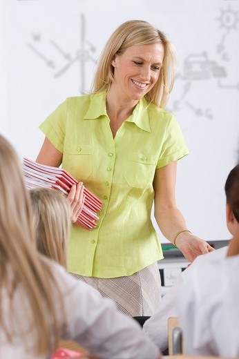 Teacher passing out test booklets to students in classroom : Stock Photo