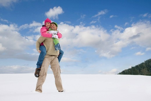 Man giving girlfriend piggyback ride through snow : Stock Photo