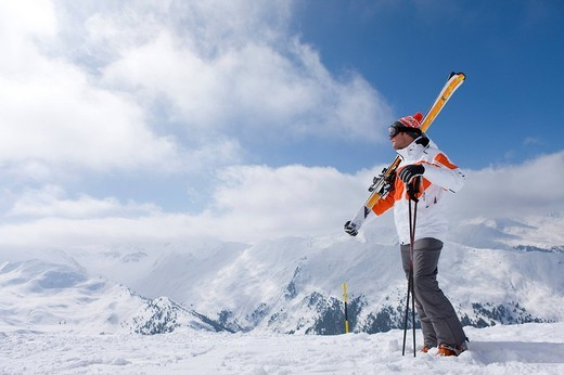 Stock Photo: 4208R-20842 Skier on remote mountain top carrying skis