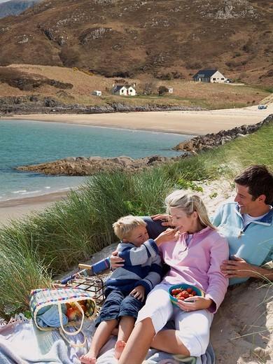 Stock Photo: 4208R-20881 Family enjoying picnic near ocean beach