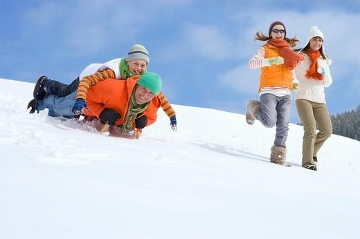 Family running and sledding down ski slope : Stock Photo