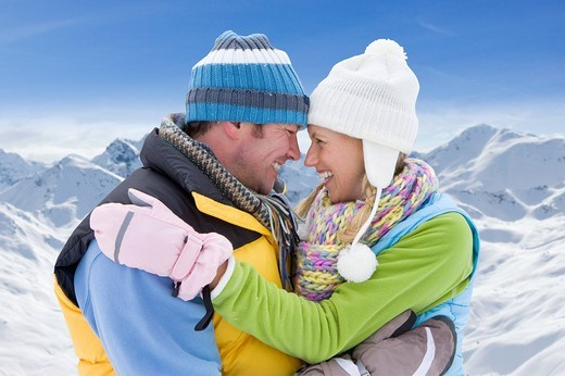 Couple hugging in snow with mountain in background : Stock Photo