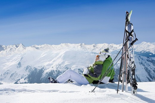 Couple sitting in snow on mountain top with skis : Stock Photo