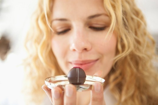 A woman holding at a chocolate : Stock Photo