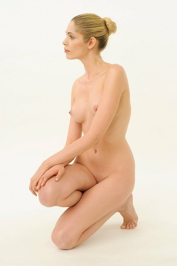A nude woman kneeling : Stock Photo
