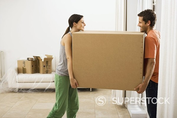 Stock Photo: 4208R-21117 Couple moving house, carrying large cardboard box in sparse room, face to face, smiling, profile