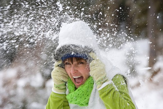 Shouting woman getting hit with snowball : Stock Photo