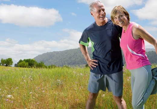 Active couple stretching before exercising in remote area : Stock Photo