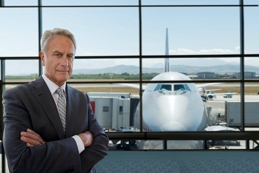 Stock Photo: 4208R-21268 Serious businessman standing in airport terminal