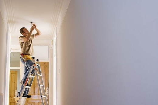 Man with toolbelt doing DIY at home, standing on step ladder, fixing light fixture in ceiling : Stock Photo