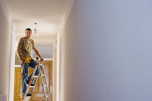 Man with toolbelt doing DIY at home, standing on step ladder below ceiling light fixture, portrait : Stock Photo