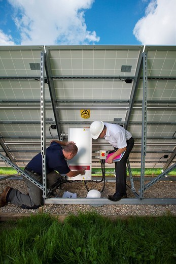 Technicians inspecting control panel on large solar panel : Stock Photo
