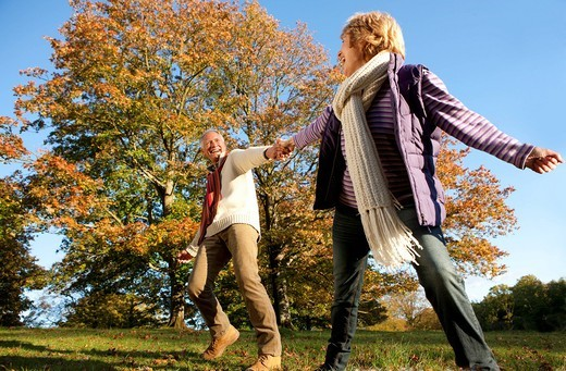 Stock Photo: 4208R-21398 Happy senior man walking and holding hands with wife in autumn