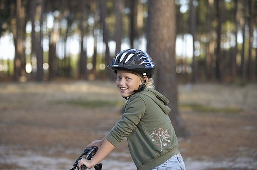 Stock Photo: 4208R-2141 Girl 8-10 wearing cycling helmet, sitting on bicycle in woodland, smiling, side view, portrait