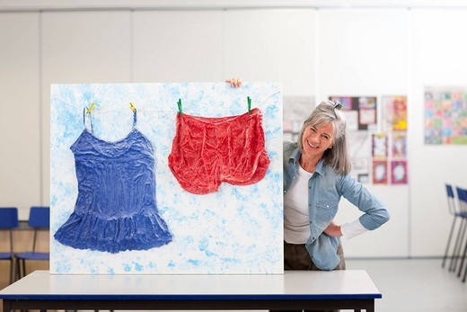 Smiling woman holding clothing artwork in classroom : Stock Photo