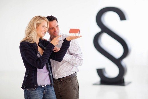 Mature couple looking at small house,  paragraph sign in background : Stock Photo