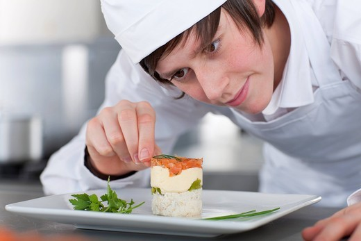 Trainee chef working in commercial kitchen : Stock Photo