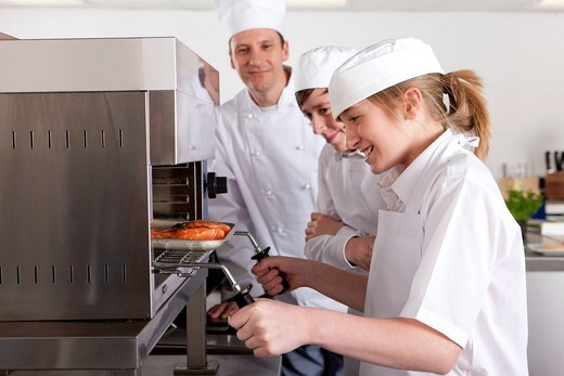 Chef watching trainee grilling food in commercial kitchen : Stock Photo