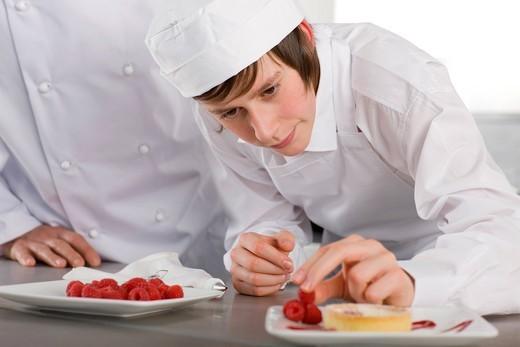Teacher watching trainee garnishing dessert in commercial kitchen : Stock Photo