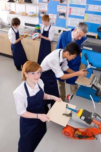 Stock Photo: 4208R-21699 Teacher watching students use saw in woodworking class
