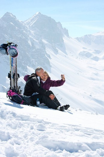 Smiling senior couple with skis taking self_portrait with digital camera on snowy mountain : Stock Photo