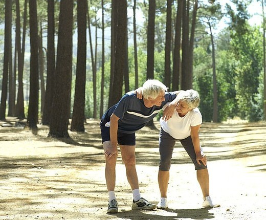 Senior couple in sportswear taking break from jogging, leaning on knees, smiling : Stock Photo