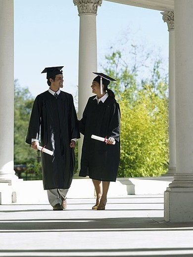 University students in graduation gowns and mortar boards walking in colonnade, holding diplomas : Stock Photo