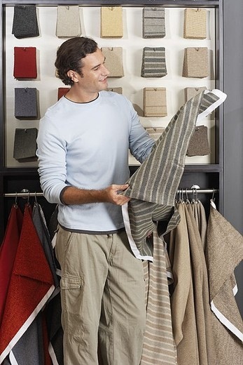 Stock Photo: 4208R-22209 Man looking at grey fabric swatch in shop, smiling, side view