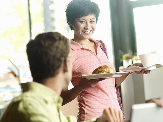 Man sitting at cafe table, focus on young woman carrying cup and plate in background, smiling : Stock Photo