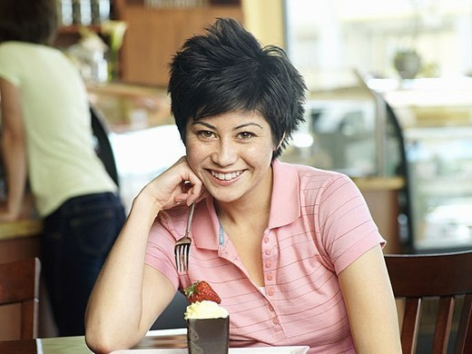 Young woman sitting at cafe table with dessert, smiling, portrait : Stock Photo