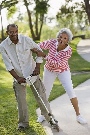 Active senior couple messing about on push scooter in park, laughing and smiling, portrait : Stock Photo
