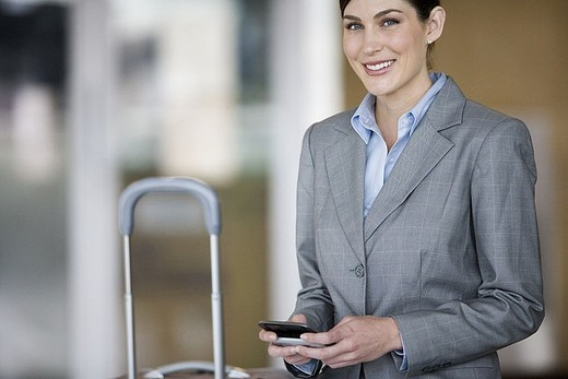 Businesswoman holding mobile phone, smiling, portrait : Stock Photo