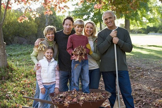 Multi-generational family standing in garden in autumn, boy 6-8 standing in wheelbarrow, smiling, portrait : Stock Photo