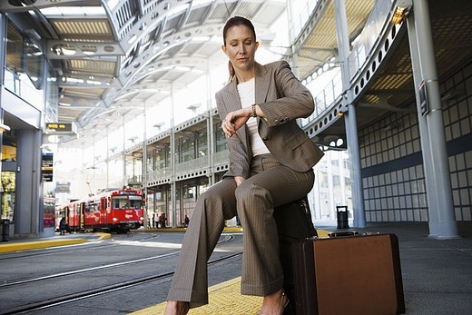 Businesswoman sitting on suitcase, waiting for city tram, checking time on wristwatch surface level : Stock Photo