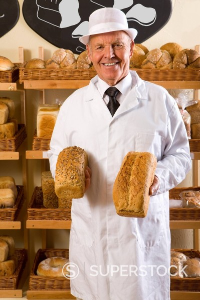 Stock Photo: 4208R-2244 Portrait of baker in white uniform holding loaves of bread