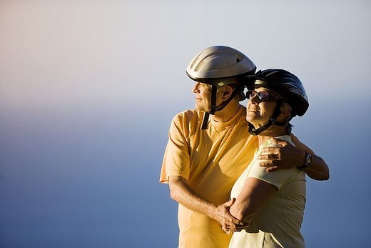 Stock Photo: 4208R-22448 Senior couple, in cycling helmets, embracing on clifftop, looking at Atlantic Ocean horizon, side view