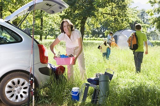 Family unloading car on camping trip, focus on woman holding pink container beside car boot, smiling, portrait : Stock Photo