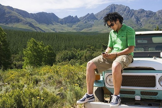 Young man sitting on bonnet of parked jeep in mountain valley, using mobile phone : Stock Photo