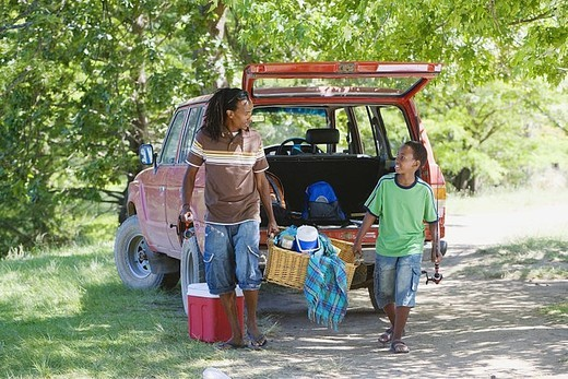 Father and son 8-10 unloading parked SUV on camping trip, sharing load of picnic hamper, smiling : Stock Photo