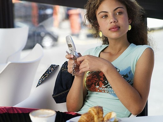 Stock Photo: 4208R-22548 Teenage girl 14-16 sitting in cafȽ, holding mobile phone, daydreaming