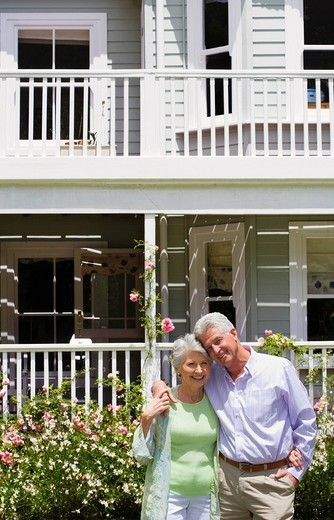 Senior couple standing in summer garden in front of house, arms around each other, smiling, front view, portrait : Stock Photo