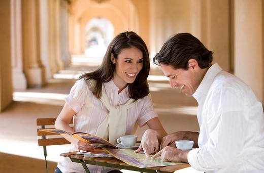 Couple sitting at pavement caf® table near colonnade, looking at tourist guide and street map, smiling : Stock Photo