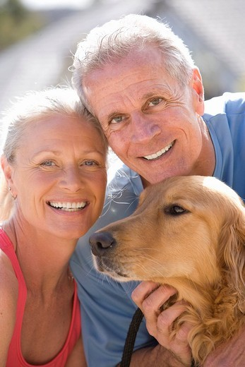 Active senior couple, in sportswear, stroking golden retriever, smiling, close-up, portrait : Stock Photo
